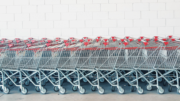 A line of push carts against a white tiled wall