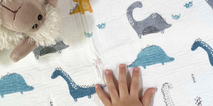 Toddler's hand on Swaddies PH Water Absorbent Bed Mat
