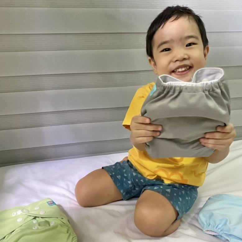 Toddler holding a cloth diaper
