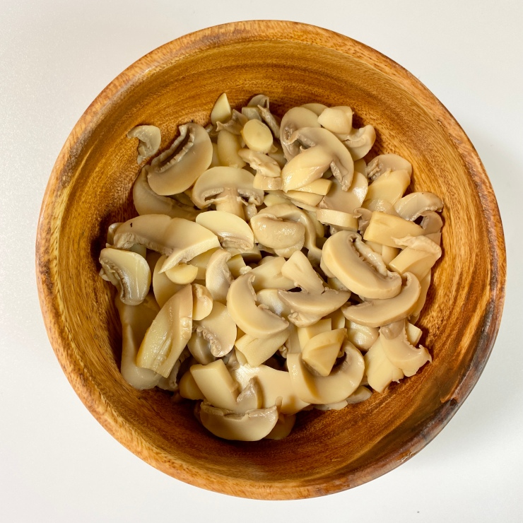 Sliced button mushrooms in a wooden bowl