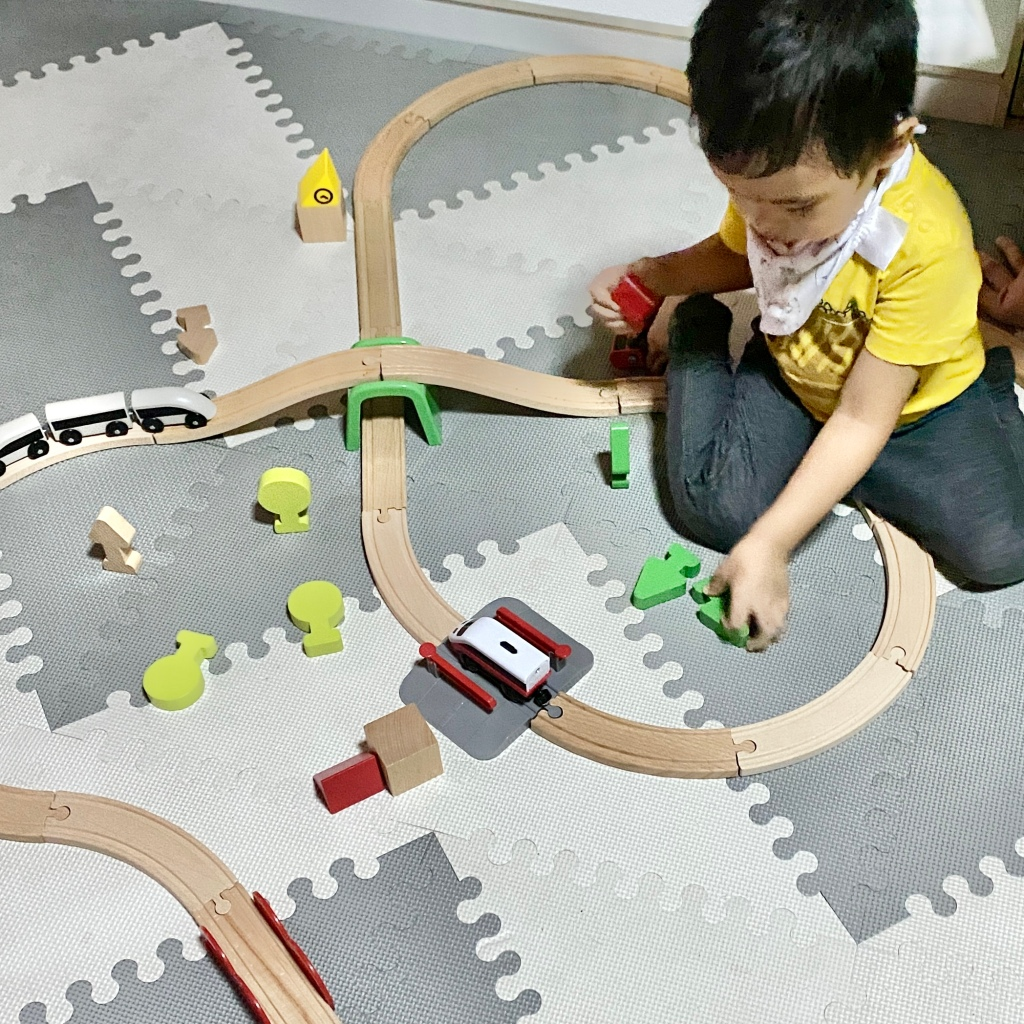 Toddler playing with wooden train tracks and toys